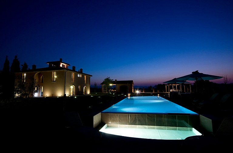 Tuscan cottage at night with infinity pool