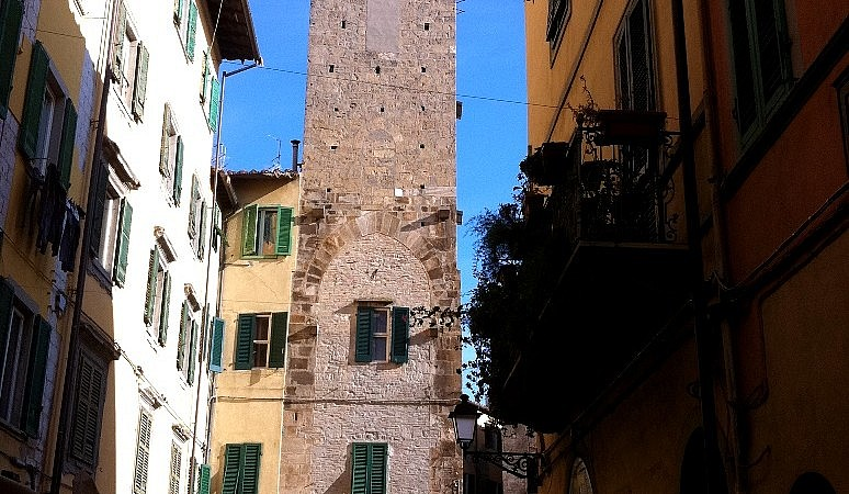 A medieval stone tower in the center of Pisa