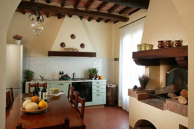 Elegant kitchen with fireplace in Tuscan country cottage for large groups