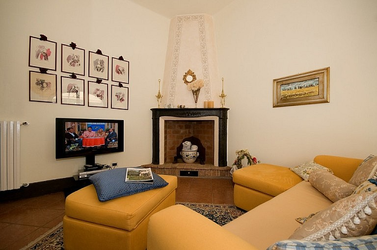 Small TV room with fireplace in Tuscan cottage