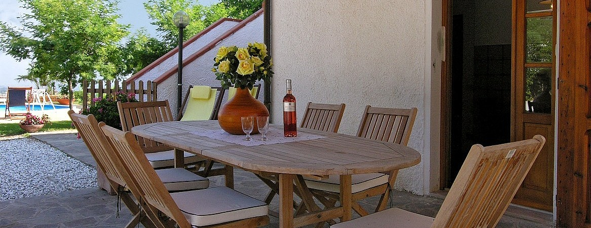 Outdoor dining area in inexpensive villa with private pool