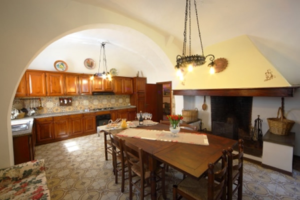 Large kitchen with Tuscan fireplace in villa for groups