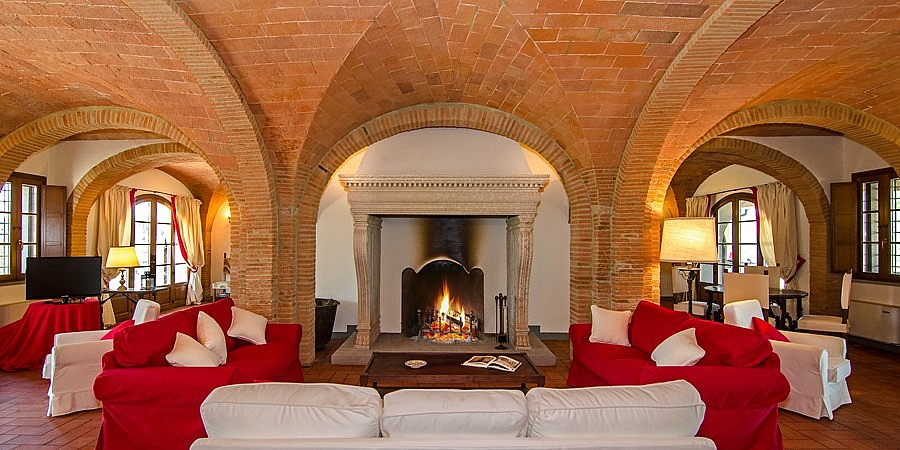 Huge Tuscan fireplace in the sitting room of villa for 20
