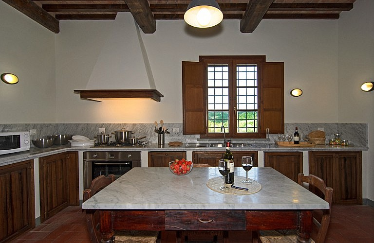 Kitchen with window over vineyards in Tuscany