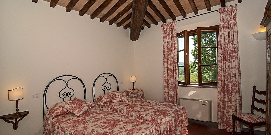 Elegant twin bedroom with view over chianti grapes
