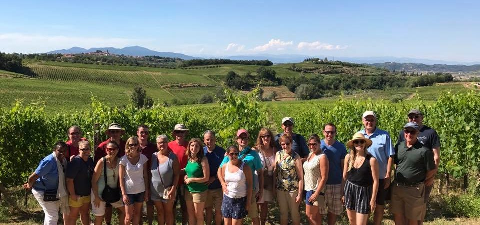 Small group posing in front of a stunning sangiovese vineyard